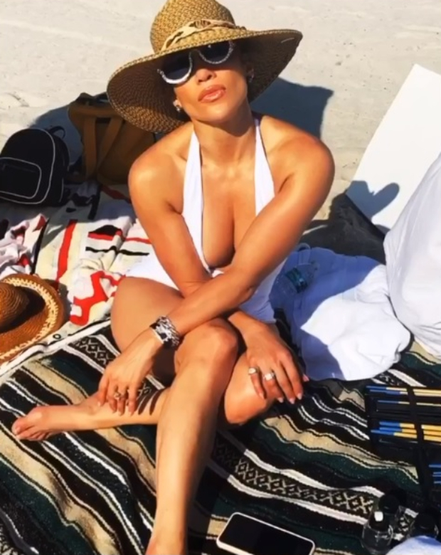 Jennifer Lopez soaks under the Miami sun flaunting her toned body in white halter-neck swimsuit